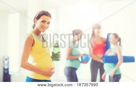 pregnancy, sport, fitness, people and healthy lifestyle concept - happy pregnant woman with water bottle in gym