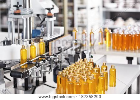 Bottles Filled With Yellow Thick Substance Standing On Desk And Conveyor Line. Production Line Of Co