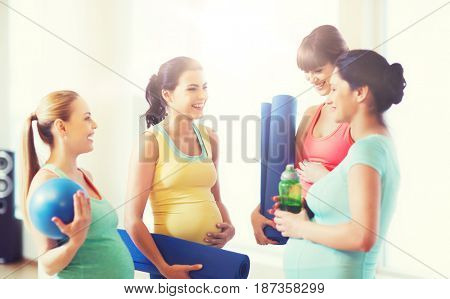pregnancy, sport, fitness, people and healthy lifestyle concept - group of happy pregnant women with sports equipment talking in gym