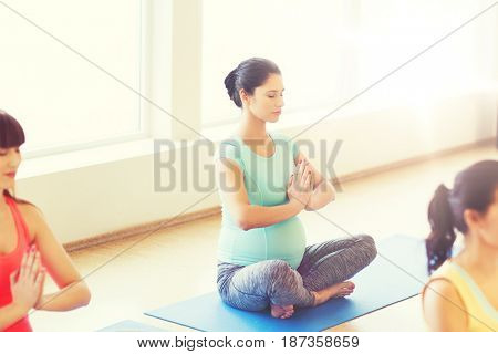 pregnancy, sport, fitness, people and healthy lifestyle concept - group of happy pregnant women exercising and meditating yoga in lotus pose in gym