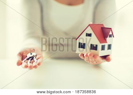 building, mortgage, real estate and property concept - close up of hands holding house model and home keys