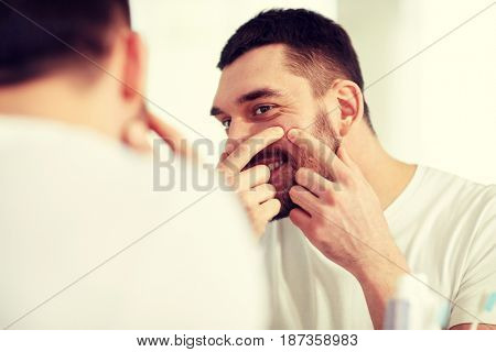 beauty, hygiene, skin problem and people concept - smiling young man looking to mirror and squeezing pimple at home bathroom