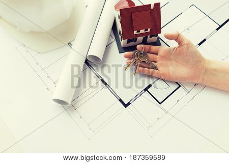 architecture, building, construction, real estate and home concept - hand with house keys and blueprint