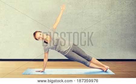 fitness, sport, people and healthy lifestyle concept - woman making yoga in side plank pose on mat over room or gym background