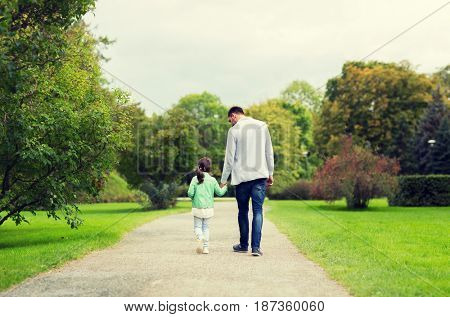 family, parenthood, fatherhood, adoption and people concept - happy father and little girl walking in summer park