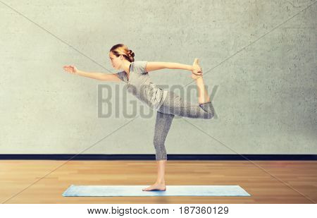 fitness, sport, people and healthy lifestyle concept - woman making yoga in lord of the dance pose on mat over room or gym background