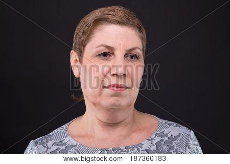 Portrait of thinking senior woman on black background