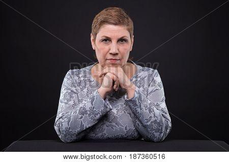 Portrait of sitting senior woman on black background