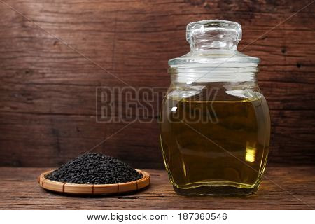 Black sesame oil in glass jar and sesame seeds on wooden table