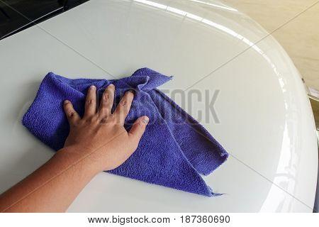 Hand with microfiber cloth polishing white car