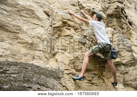 The lean guy in the hat of shorts and a T-shirt is engaged in rock climbing on a steep rock without insurance