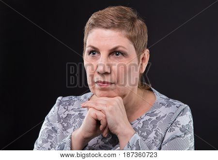 Portrait of sitting senior woman looking side on black background