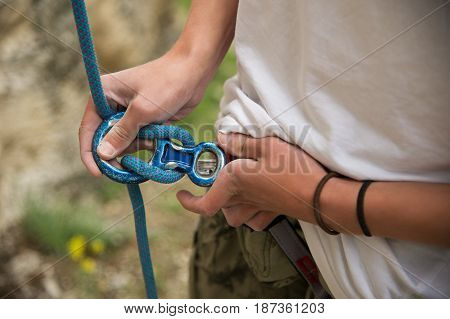 Close up Portrait of young man preparing the equipment for climbing.