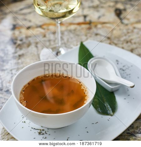 Japanese cuisine. Miso soup in white ceramic bowl served with green leaf, sppon and glass of white wine on marble table.
