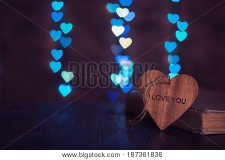 Wooden heart with the word love and background with a back of the heart