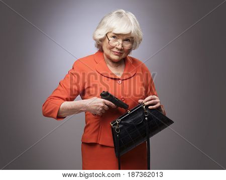 Senior woman putting a gun in her small handbag self defence concept