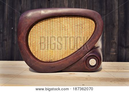 Old brown vintage bakelite Tesla radio on wooden background