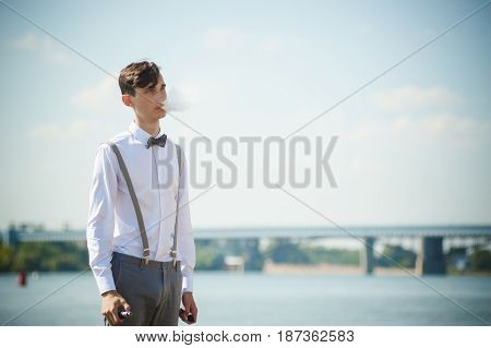 Young Skinny Man, Elegantly Stylishly Dressed In White Shirt, Trousers With Suspenders And Bow Tie.