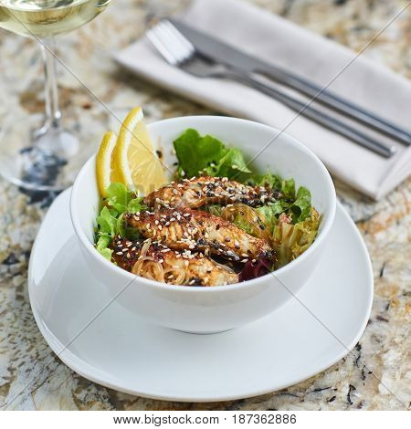 Asian cuisine. Warm salad with eel fish and rice served in white ceramic bowl with knife, fork and glass of white wine on marble background