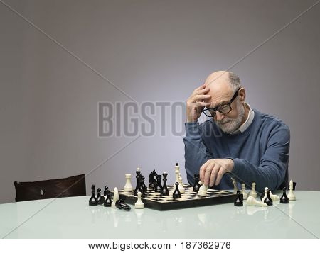 Senior man thinking over his move in chess studio shot on gray background with copy space