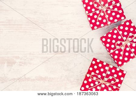 Red dotted gift boxes scattered over white wood background. Copy space.