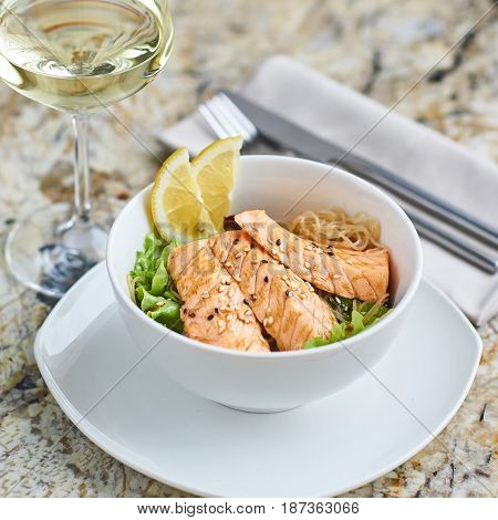 Asian cuisine. Warm salad with salmon fish and rice served in white ceramic bowl with knife, fork and glass of white wine on marble background