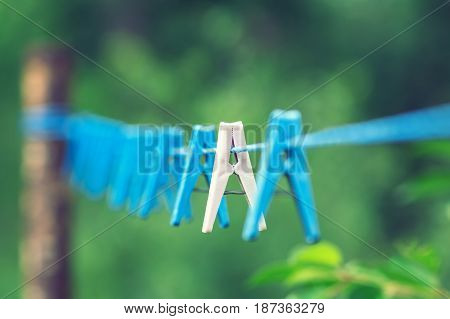 Linen clothespins on a rope with a focus on one clothespin