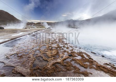 geyser field tatio with water surface at sunrise in atacama desert, chile