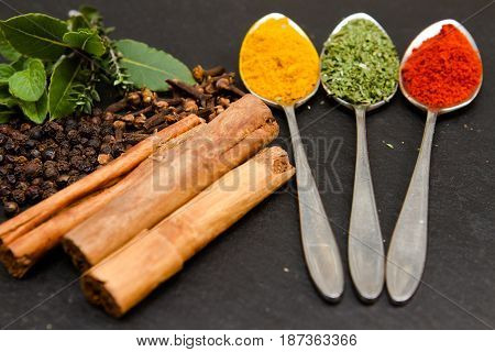 Spices Three teaspoons each containing a different spice with cinnamon, bay and thyme