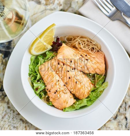 Asian cuisine. Warm salad with salmon fish and rice served in white ceramic bowl with knife, fork and glass of white wine on marble background. Flat lay or top view.