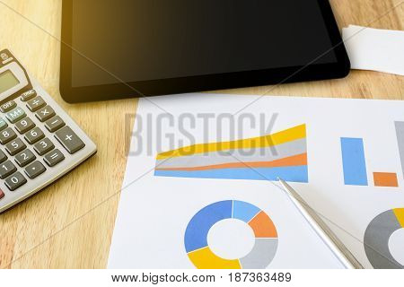 financial colorful graph with calculator and tablet soft light effect