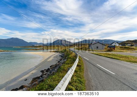 Asphalt road along the beach and sea with blue sky fjord Norway