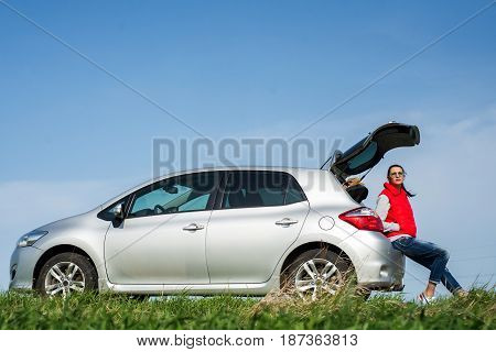 Woman near the car, with her baggage.