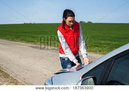 young brunette girl near broken car with open hood.