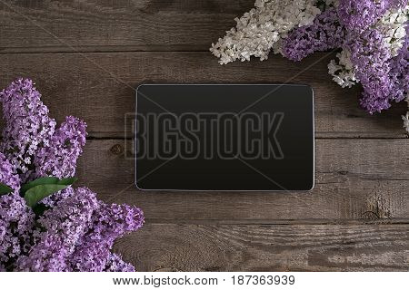 Lilac blossom on rustic wooden background, tablet with empty space for greeting message. Top view. Mother's Day. Spring background concept.