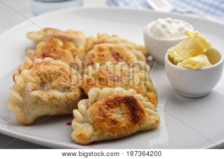 Traditional Polish dumplings Pierogi ruskie with sour cream and butter on a rustic table