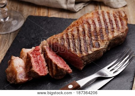 Grilled marbled beef steak on a slate cutting board