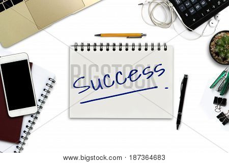 Success on notepad - White office desk with smartphone with black screen pen laptop computer notepad and supplies. - Top view image.