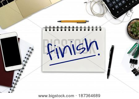 finish on notepad - White office desk with smartphone with black screen pen laptop computer notepad and supplies. - Top view image.