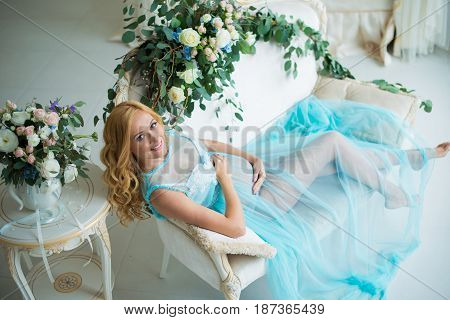 The most charming pregnant girl in a gentle interior with fresh flowers