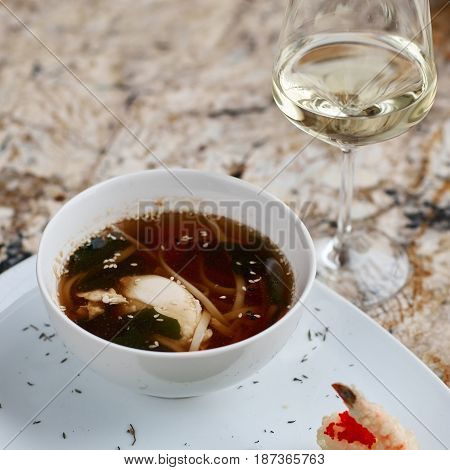 Japanese cuisine. Noodle soup udon in white ceramic bowl served with spoon, glass of white wine and king prawn on marble table