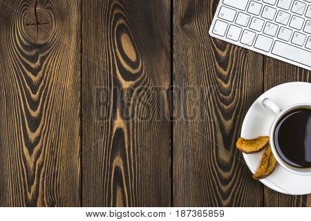 Office desk with copy space. Digital devices wireless keyboard and mouse on dark wooden table with cup of coffee top view
