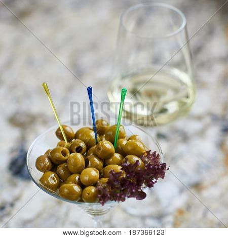 Appetizer. Green olives served in martini glass with glass of white wine on marble table