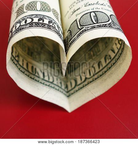 Hundred dollar bill in heart shape on red
