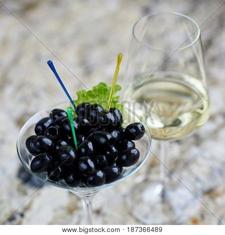 Appetizer. Black olives served in martini glass with glass of white wine on marble table