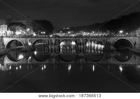 Ponte Sant Angelo, bridge in Rome at night time. Italy. Black and white. Once the Aelian Bridge or Pons Aelius, meaning the Bridge of Hadrian, is a Roman bridge in Rome, Italy.