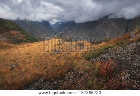 The picturesque autumn landscape with mountains and low sky covering the tops of the mountains, Altai region, Siberia, Russia