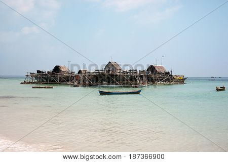 Man made fishing island with fishing nets to catch fish with and small houses floating near the blue ocean coast next to white sand beach surrounded by small wooden fishing boats in the morning.