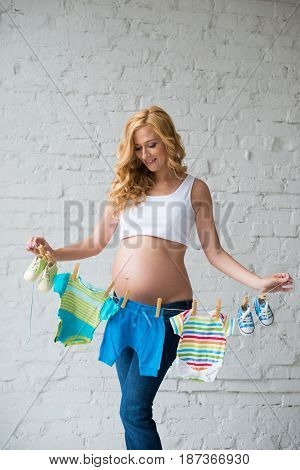 Pregnant woman posing with children's clothes on a brick wall background
