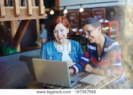 Smiling old buddies talking to relatives in video-chat